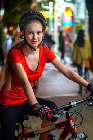 City night bicycle ride. Girls wearing bicycle helmet.