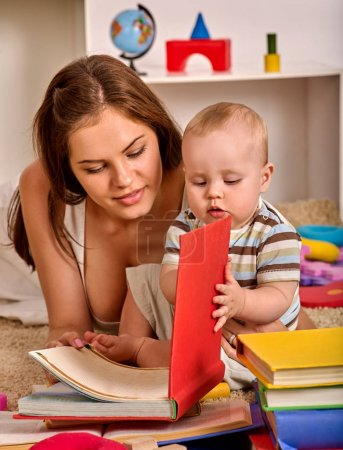 Kid and mother baby boy lying on floor and read book.