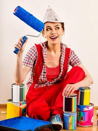 Repair home woman holding paint roller for wallpaper.