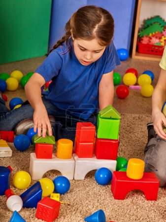 Children building blocks in kindergarten. Group kids playing toy floor.
