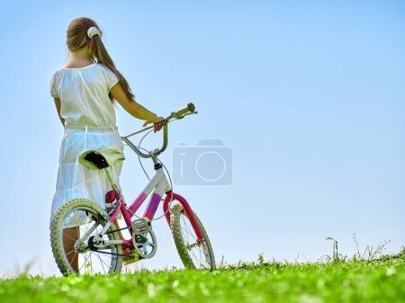 Child girl wearing white skirt rides bicycle into park.