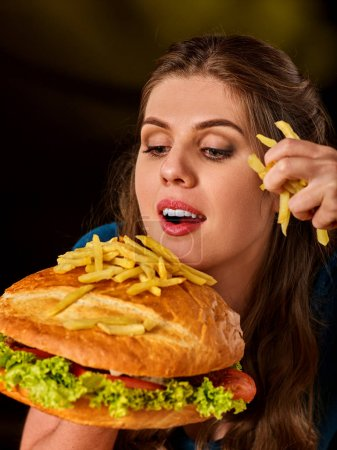 Woman eating french fries and hamburger.