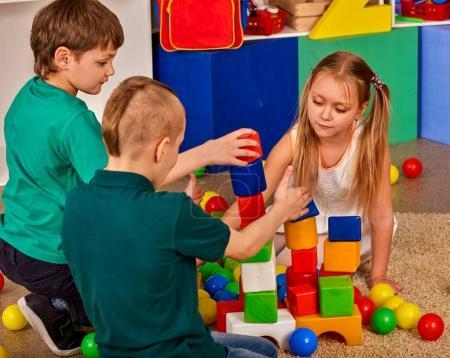 Children building blocks in kindergarten. Group kids playing toy floor.