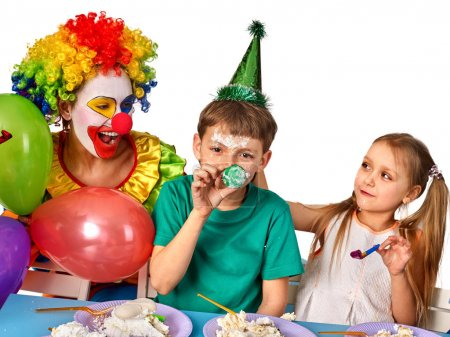 Birthday child clown eating cake with boy together. Kid with messy face.