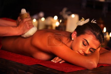 Spa gifts of woman massage in spa salon. Female have herbs hot ball therapy.