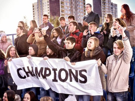 Cheering fans in stadium holding champion banner.