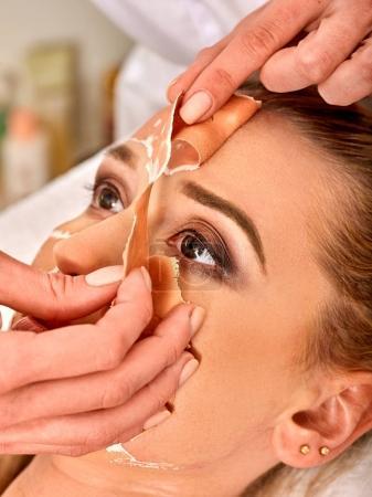 Collagen face mask. Facial skin treatment. Woman receiving cosmetic procedure.