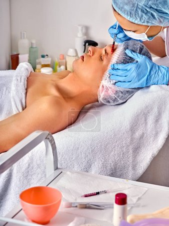 Dermal fillers of man in spa salon with beautician.