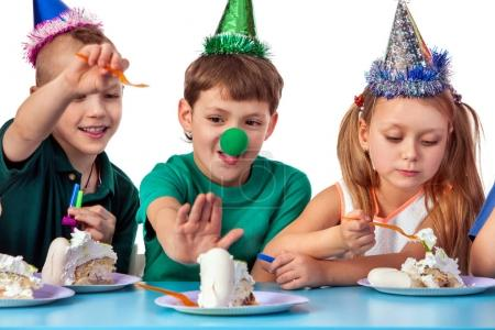 Birthday children celebrate party and eating cake on plate together.