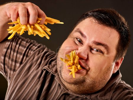 Fat man eating fast food french fries for overweight person.