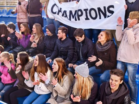 Cheering fans in stadium holding champion banner.