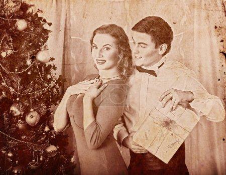 Christmas nostalgy couple on party near Xmas tree take gift box.