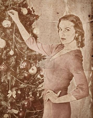 Photo for Nostalgy Christmas woman dressing Xmas tree. Woman hangs up last decoration ball . She turns her face and looking at camera. Home portrait vintage sepia old retro photo 1910-1940. - Royalty Free Image