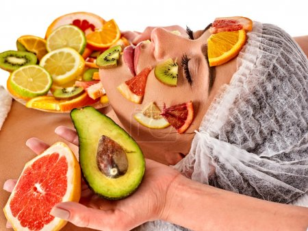 Facial mask from fresh fruits for woman . Beautician apply slices.