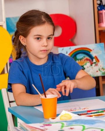 Photo for Small students painting in art school class. Child drawing by paints on table in kindergarten. Newcomer in a childrens team. Girl dreams of spring and summer. - Royalty Free Image