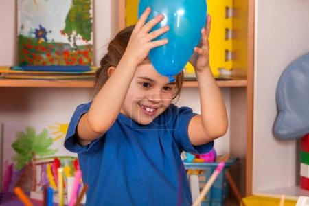 Photo for Break school in painting class. Physical education of little girl playing with balloon. Craft drawing develops creative abilities of children. Newcomer in a childrens team. - Royalty Free Image