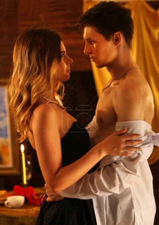 Couple dancing and kissing indoor in romantic interior.