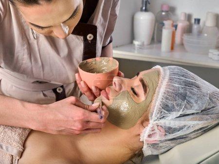 Mud facial mask of woman