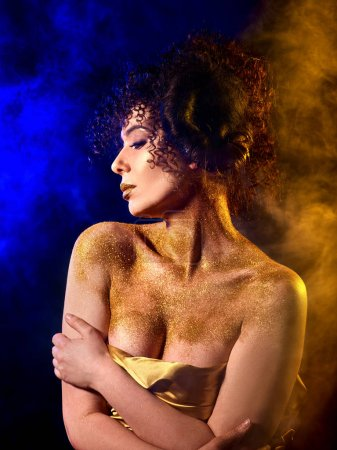 Golden powder cosmetics on bare woman shoulders with decorative.