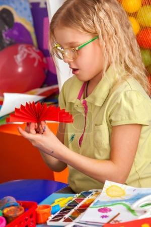 School children with scissors in kids hands cutting paper.