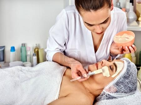 Photo for Collagen facial mask of mud of dead sea for skin treatment. Face of woman of elderly woman 50-60 years old receiving cosmetic procedure in beauty salon close up . Professional beautician. - Royalty Free Image