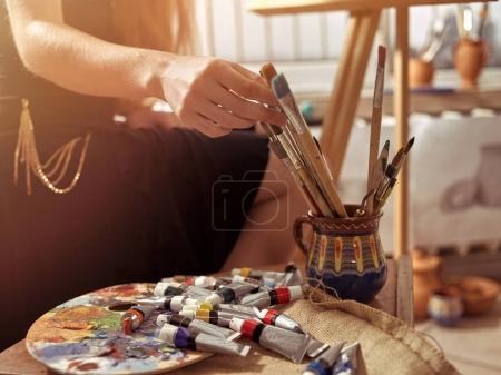 Pintura de artista sobre caballete en estudio. Pinturas de niña con pincel .