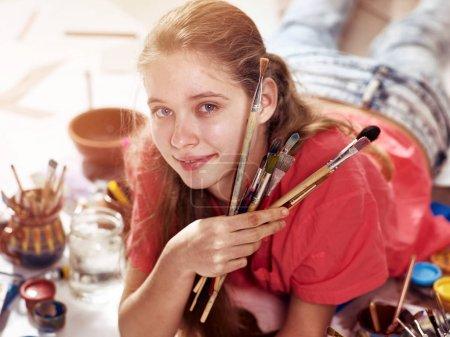 Authentic artist children girl paints on floor. Top view.