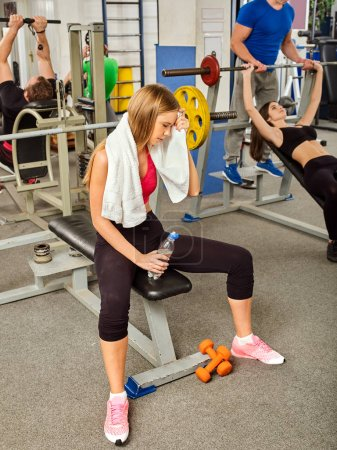 Woman in gym workout fitness equipment. Girl drink bottle water.