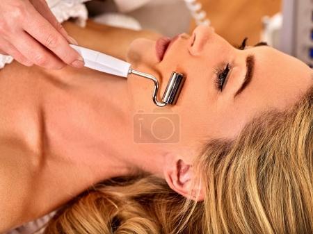 Facial massage at beauty salon. Electric stimulation woman skin care.