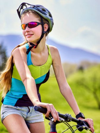 Photo for Woman traveling bicycle in summer park. Womens road bike for running on green grass aganist blue sky with white clouds. Female in school trip. Girl keeps herself in good shape. - Royalty Free Image