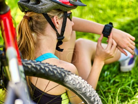 Photo for Woman traveling bicycle in summer park. Bicyclist girl watch on smart watch. Girl counts pulse after sport training. Cycling is good for health. School trip. - Royalty Free Image