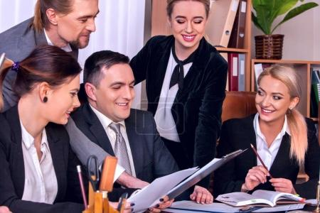 Foto de Negocios personas oficina vida de equipo personas trabajando con papeles sentado a mesa. Armarios con carpetas y cortinas, flores en el fondo de macetas. La firma aumentó sus ingresos por año - Imagen libre de derechos