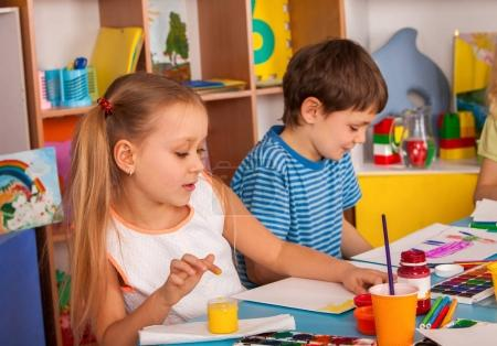 Small students girl and boy painting in art school class.