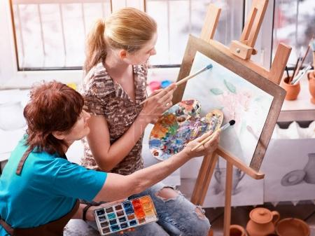 Artista pintando caballete en el estudio. Abuela y niños auténticos .