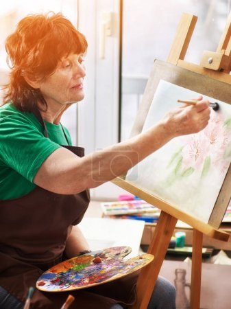 Artist painting easel in studio. Authentic senior woman.