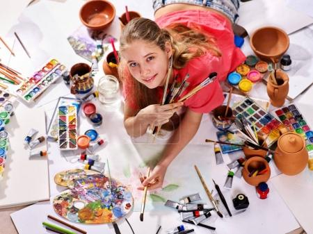 Photo for Authentic artist children girl paints with set palette watercolor paints palette and brush in morning sunlight. Painting in studio on floor. Best choice of brushes for watercolor painting. - Royalty Free Image