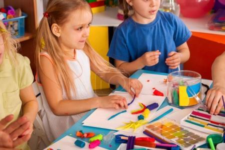 Photo pour Pâte à modeler modeler en classe des enfants. Professeur enseigne enfants jouer ensemble la pâte et le moule de pâte à modeler en maternelle ou école maternelle. Groupe de quatre personnes. Exposition de l'école. - image libre de droit