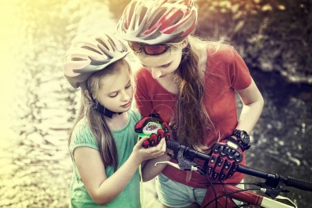 Photo for Bikes cycling weekend for girls. Children training rides bicycle in cycling look at compass. People lost their way traveling unaccompanied. Toning photo of school trip. Effect of film. - Royalty Free Image