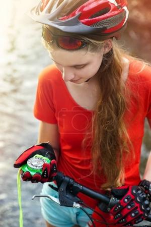 Photo for Bicycle compass training in hands female. Cyclist look at compass and looking for way. People lost their way traveling unaccompanied. Girl in school trip. - Royalty Free Image