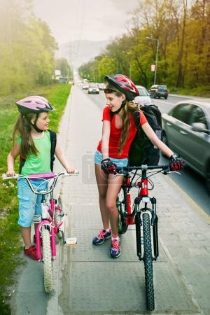 Photo for Bikes bicycle girl wearing bicycle helmet and glass with rucksack ciclyng. Children cycling on yellow bike lane at city street. Unexpected meeting of friends. Kids are advised about route. - Royalty Free Image