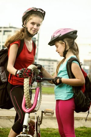 Photo for Bicycle tire pumping and repair by child bicyclist. Girl repairing bicycle on road . Kids pump up tire. Children return home from school on bicycles. Tone image. They help children repair bicycles. - Royalty Free Image