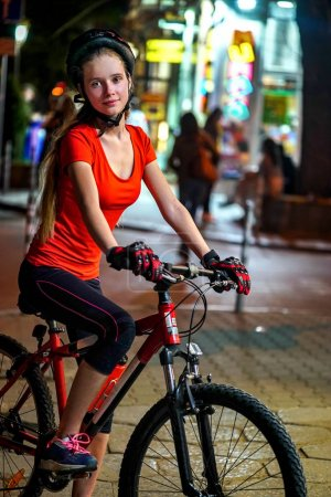 Photo for City night bicycle ride. Girls wearing bicycle helmet. Nightlife and passer people in city background. Luminous windows and group people in background. - Royalty Free Image