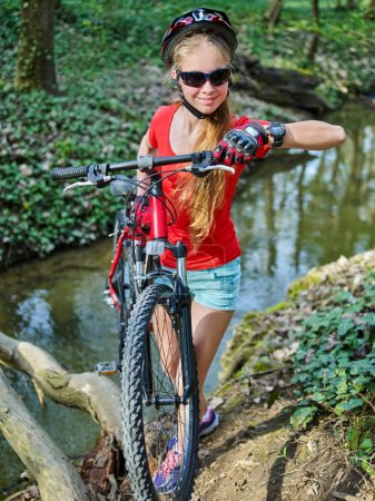 Photo for Bicycle teen with ladies bikes in summer park. Womens road bike for running on nature. Teenager girl in helmet cycling fording throught water. Cycling trip is good for health outdoor. Childrens camp. - Royalty Free Image