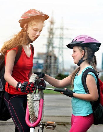 Photo for Bicycle tire pumping by child bicyclist. Girl wearing bicycle helmet with hand pump. Kids pump up tire. There are road and traffic sign at background. Children return home from school on bicycles. - Royalty Free Image