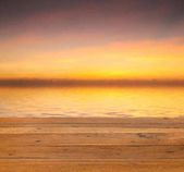 Sunset over calm off wooden deck