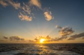 Sunset behind a cruising cruise ship at sea