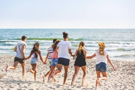 Photo for Multiracial group of friends running on the beach. Four girls and three boys, wearing trunks and colourful t-shirts, having fun at seaside. Friendship and lifestyle concepts. - Royalty Free Image