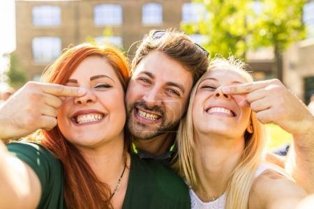 Photo pour Groupe d'amis s'amuser ensemble au parc et en prenant un selfie. Heureuse filles et un garçon souriant et regardant la caméra. Concepts de mode de vie et d'amitié - image libre de droit