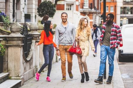 Photo for Multiracial group of friends walking in London. Two couples, talking and laughing. Residential district with houses and cars on background. Lifestyle and friendship concepts. - Royalty Free Image