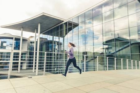 Woman jogging, panning view with modern buildings on background